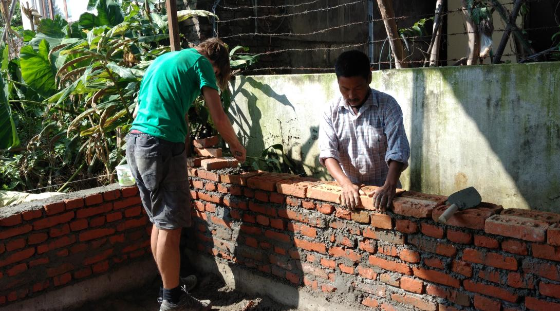 A Building volunteer and a local builder construct a classroom wall in Nepal during the building volunteering project abroad